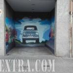 Puerta metálica parking en Guinardó decorada con coche Seat 600 en graffiti - ArteExtra